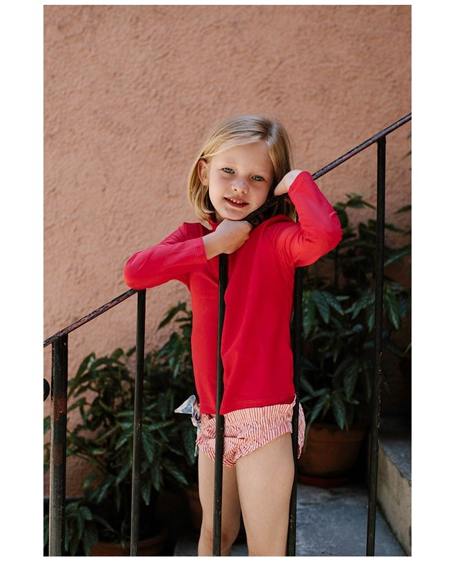 Girl wearing a sun protective rashguard in Fragola red for children