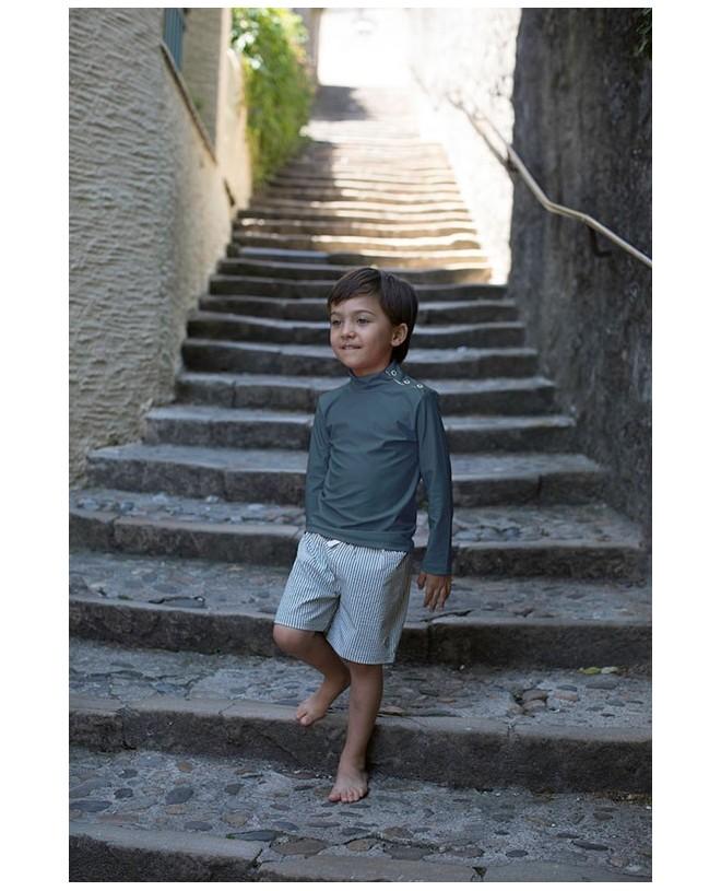 Boy wearing the Pine Green seersucker swim shorts by Canopea